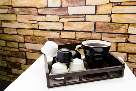 A cup of black coffee with capsules for coffee machine on stone background
