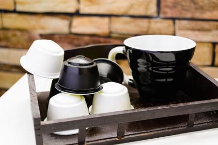Een kopje zwarte koffie met capsules voor koffiemachine op stenen achtergrond Stockfoto