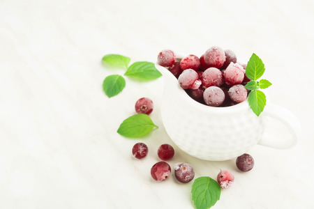Frozen cranberry in white sauce pan with fresh mint over light table with copy space