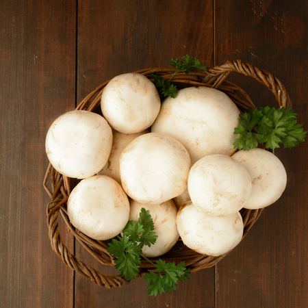 table top: Basket with champignon and greens, top view, square shot