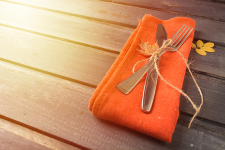 Toned fall serving perspective table with fork, knife and orange napkin over wooden background Copy space Stock Photo