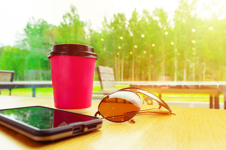 Coffee, phone and sunglasses on brown table in cafe on the road with green nature outside and lights reflection in window Toned photo