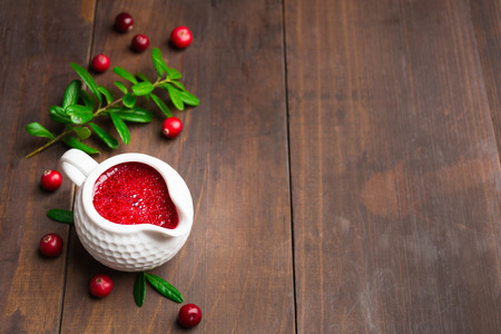 Lingonberry sauce in ceramic saucepan on wooden background with copy space Stock Photo