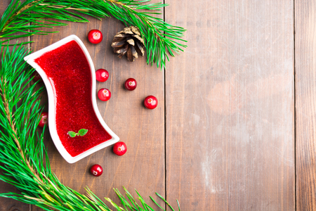 Cranberry sauce with christmas decoration over wooden table with copy space Stock Photo