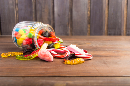 Mix colorful candies in glass jar in wooden background with copy space, selective focus Stock Photo