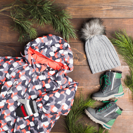 Winter clothes with jumpers, knitted hat and gloves and boots over wooden background with fir tree decoration, flat lay