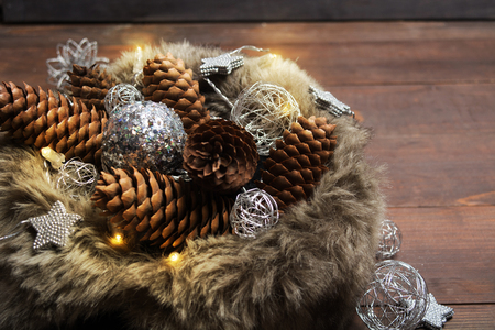Winter holiday lights with pine cones and ornaments in fur  on wooden background
