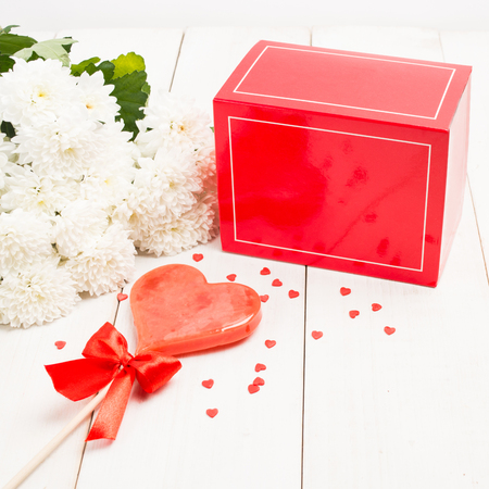 Red gift box, flowers and sweet heart lollipop on wooden background, Valentines Day concept