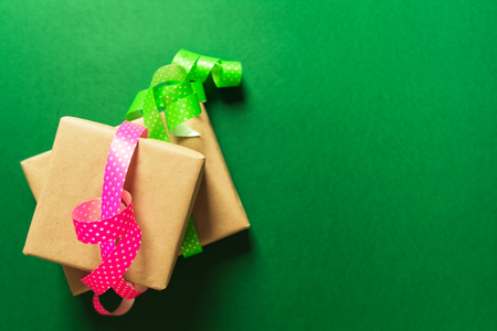 Wrapping gifts in craft paper with ribbons over green background, flat lay Stock Photo