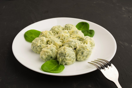 Spinacj and cheese gnocchi on white plate with fork over grey background