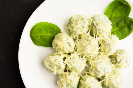 Cheese spinach gnocchi on white plate, closeup view, overhead view Stock Photo