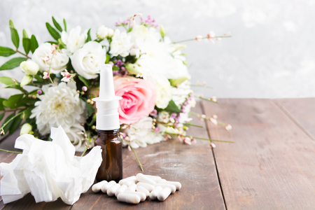 Seasonal allergy concept with spray, pills and wrinkled tissue on wooden table with copy space Stock Photo