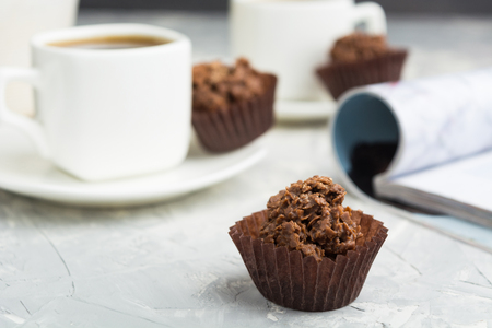 Chocolate candies with nuts and shinning topping on grey background with coffee, selective focus
