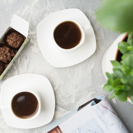 Coffee for couple and sweet dessert in box in cafe on grey background with plant, overhead view, flat lay, square shot Banque d'images