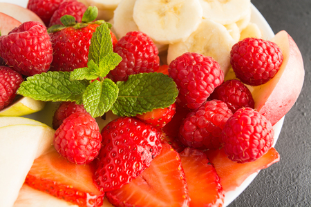 Closeup view of fresh berries, bananas, apples and mint leaves on plate