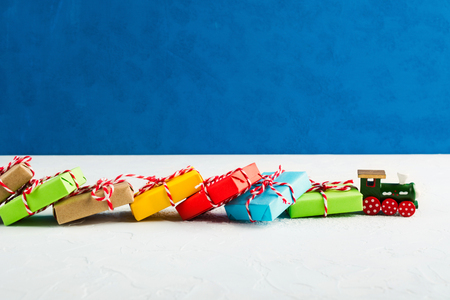 Train transports many colorful Christmas gifts in paper with blue background, copy space