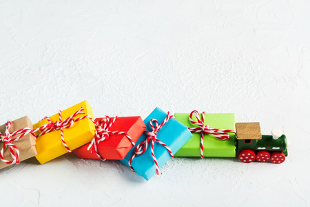 Green wooden train haul Christmas colorful gifts on white background, copy space