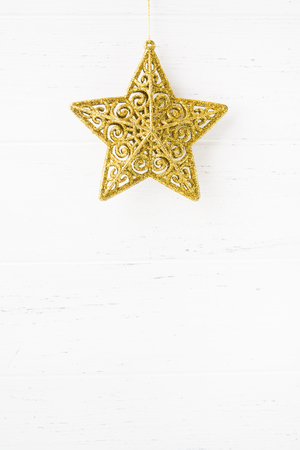Christmas golden star ornament on white wooden background with copy space Stock Photo