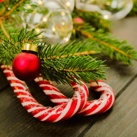 Closeup view of Christmas candy cane with fir tree and ornament ball, soft focus, square Stock Photo