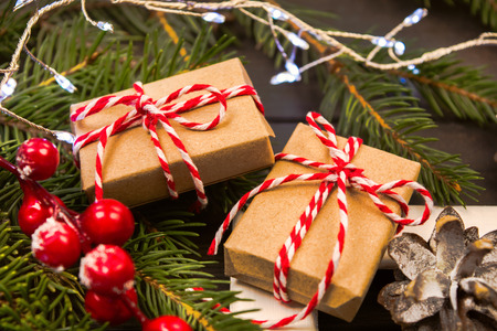 Two wrapped in craft paper presents on natural fir tree with christmas decorations, soft focus
