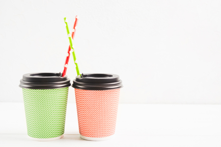 Green and red paper cups with plastic cover and paper straw