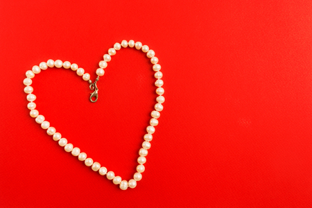 Heart shape of white pearl necklace on red background, Valentine's Day concept, flat lay