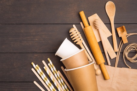 Wooden and paper eco-friendly kitchenware over wooden background with copy space, flat lay