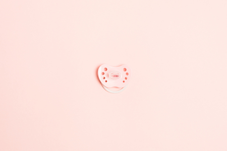 Pastel pink plastic baby pacifier on pink background, flat lay, copy space, top view