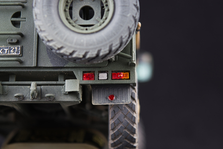 Russian military armored camouflage jeep Tiger. Closeup view. Plastic scale model on dark background. Back view with spare wheel Stock Photo
