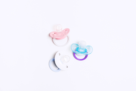 Three colorful baby silicone pacifier with holder in center on white background. Mock up. Flat lay. Top view. Orthodontic equipment for baby