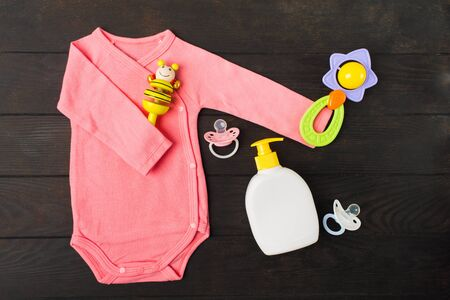 Pink bodusuit holding two rattles and two sylicone pacifiers with baby soap on brown wooden background. Top view. Flat lay Standard-Bild