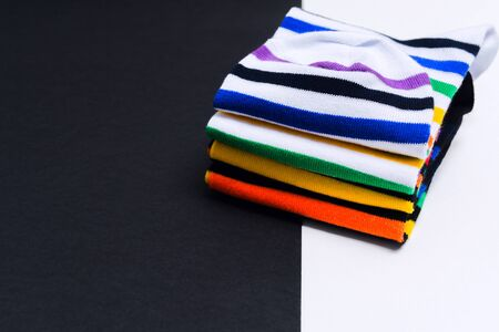 Set of colorful striped white and black socks on white and black background with copy space. Selective focus. Warm funny clothes for hipster