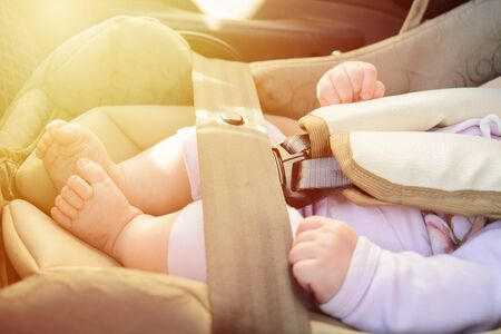 Safety concept, protection of child in travel, children feet in baby seat. Small newborn baby sitting in special car seat with safety seatbelts. Sunlight