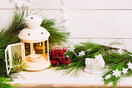 Open white lantern with caandle adn natural fir tree branches with toy house. Christmas room decoration. Copy space. Interior design