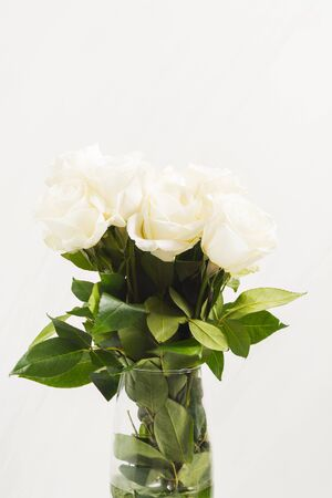 Beautiful white roses in bouquet in glass vase.Present for Valentines Day, wedding or arrangement holiday. Vertical shot