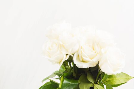Bouquet of white roses on white background with copy space. Valentines day, wedding or romantic concept