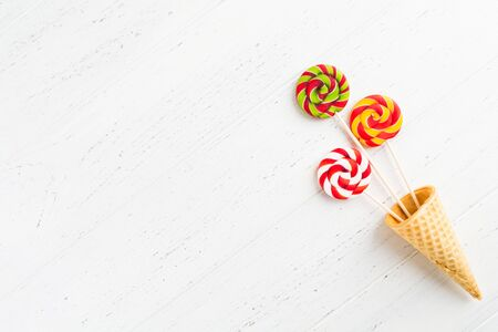 Waffle cone with round colorful lollipops on sticks. Colorful sweets over white wooden background with copy space. Flat lay top view