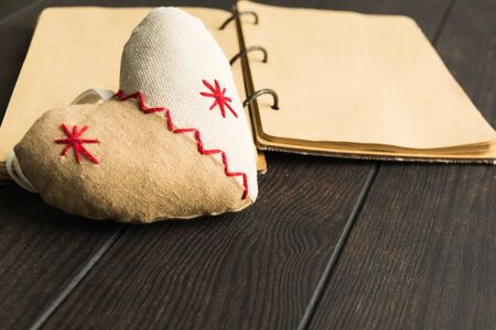 Soft heart made from textile with open notebook on background over brown wooden table with copy space. Selelctive focus