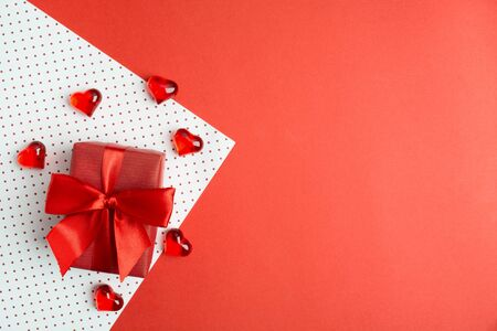 Red gift box with bow on wrapping paper with hearts. Valentine's day's cocncept. Copy space. Flat lay. Top view