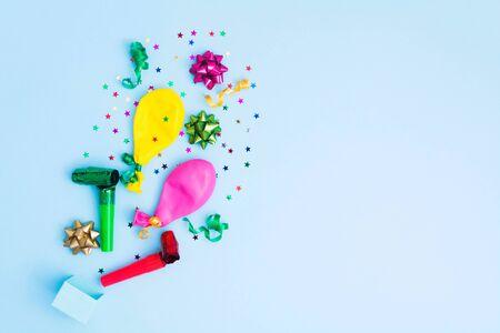 Fond d'anniversaire bleu avec des arcs colorés, des ballons, des banderoles et des confettis décoller de la boîte-cadeau. Espace de copie. Mise à plat