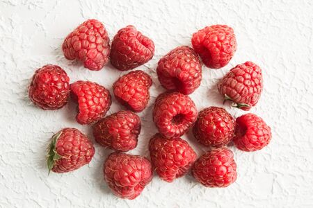 Stack of fresh red raspberries over white textured background. Flat lay 写真素材