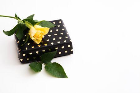 与黑纸的美丽的礼物与金黄心脏和唯一黄色在白色背景上升了。复制空间。选择性焦点。情人节概念
