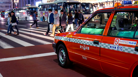 SHINJUKU, TOKYO  JAPAN - MARCH 26, 2018: A taxi stopping on a red light to give way on the pedestrians Editorial