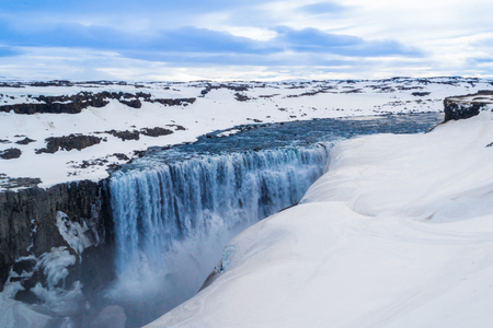 blu sky: deltifoss, the most powerful waterfall in europe, it is in Iceland during winter with snow floo and blu sky