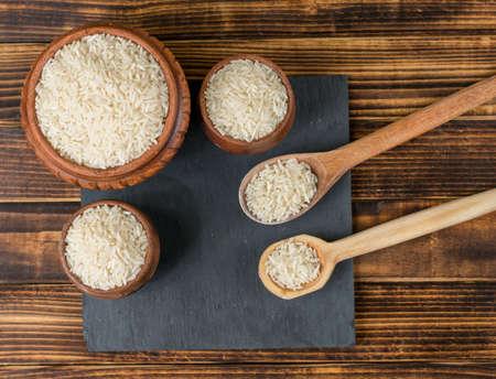 Uncooked rice over kitchen utensils and dark wood