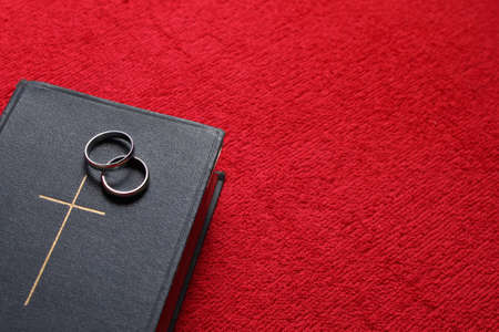 Bible with a pair of wedding rings on red background