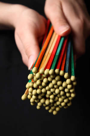 Bundle of colored matches in womans hands