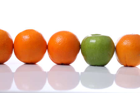 Row of oranges infiltrated by a green apple