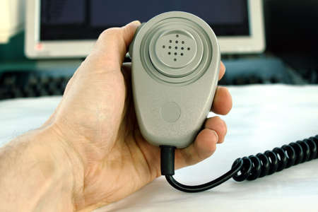 Hand holding radio microphone with computer screen and keyboard in the background