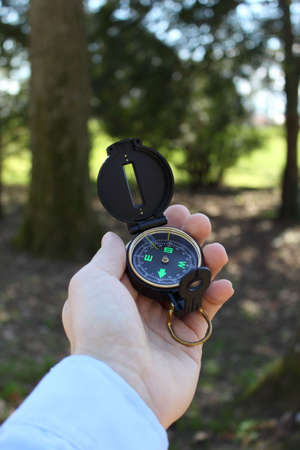 Male hand holding compass in forest, vertical orientation